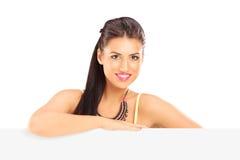Presentación femenina hermosa sonriente detrás de un panel Foto de archivo libre de regalías