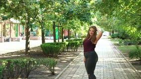 Presentación gorda modelo de la muchacha en un parque soleado de la ciudad del verano Cámara lenta almacen de metraje de vídeo