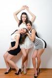 Presentación hermosa elegante de tres muchachas aislada en blanco Foto de archivo