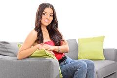 Presentación hermosa joven de la muchacha asentada en un sofá Fotos de archivo