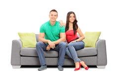 Presentación joven de los pares asentada en un sofá moderno Foto de archivo libre de regalías