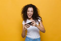 Presentación linda feliz de la mujer joven aislada sobre juegos amarillos del juego del fondo con el teléfono móvil fotos de archivo