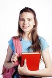 Presentación linda joven del adolescente alegre contra el fondo blanco con los libros y la mochila Fotos de archivo