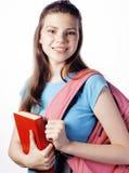 Presentación linda joven del adolescente alegre contra el fondo blanco con los libros y la mochila Imágenes de archivo libres de regalías