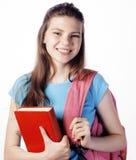 Presentación linda joven del adolescente alegre contra el fondo blanco con los libros y la mochila Imagenes de archivo