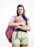 Presentación linda joven del adolescente alegre contra el fondo blanco con los libros y la mochila Fotografía de archivo