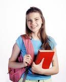 Presentación linda joven del adolescente alegre contra el fondo blanco con los libros y la mochila Fotografía de archivo libre de regalías