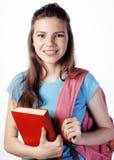 Presentación linda joven del adolescente alegre contra el fondo blanco con los libros y la mochila Imagen de archivo libre de regalías