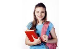 Presentación linda joven del adolescente alegre contra el fondo blanco con los libros y la mochila aislados Imagen de archivo libre de regalías