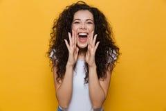 Presentación linda joven emocionada de griterío de la mujer aislada sobre fondo amarillo fotografía de archivo libre de regalías