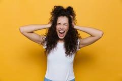 Presentación linda joven emocionada de griterío de la mujer aislada sobre fondo amarillo imagen de archivo