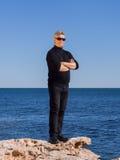Presentación madura del hombre de negocios confiada en una roca en el mar Imágenes de archivo libres de regalías