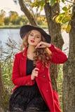 Presentación modelo de la muchacha en una capa roja y un sombrero negro en las ramas de un árbol en la orilla del río Imágenes de archivo libres de regalías
