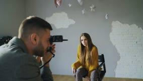 Presentación modelo de la mujer hermosa joven para el fotógrafo mientras que él está tirando con una cámara digital en estudio de imagen de archivo