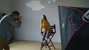 Presentación modelo de la mujer hermosa joven para el fotógrafo mientras que él está tirando con una cámara digital en estudio de Fotos de archivo libres de regalías