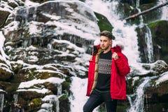 Presentación modelo del individuo cerca de la cascada en montañas del invierno Fotografía de archivo
