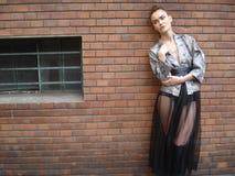Presentación modelo femenina delante de la pared de ladrillo Fotografía de archivo