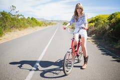 Presentación modelo joven alegre mientras que monta la bici Fotografía de archivo