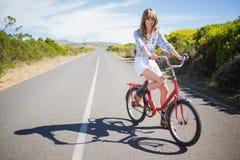 Presentación modelo joven sonriente mientras que monta la bici Imagenes de archivo