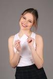 Presentación modelo sonriente con la nota Cierre para arriba Fondo gris Foto de archivo libre de regalías