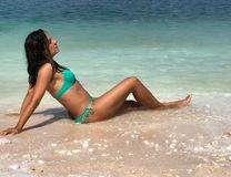 Presentación morena atractiva en la playa foto de archivo