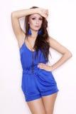 Presentación morena atractiva en vestido azul. Foto de archivo