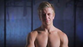 Presentación muscular feliz del hombre descamisada en el gimnasio que sonríe y que ríe metrajes