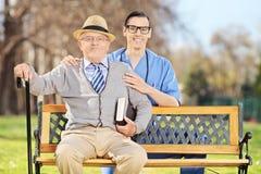 Presentación profesional de la atención sanitaria con un hombre mayor Imagen de archivo libre de regalías
