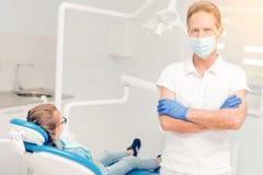 Presentación profesional dental confiada con sus brazos cruzados Imagen de archivo libre de regalías