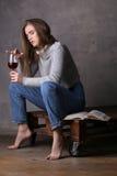 Presentación rubia con el libro y el vidrio de vino Fondo gris Fotografía de archivo libre de regalías