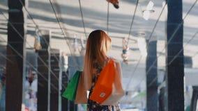 Presentación shopaholic de la muchacha alegre joven con el bolso de compras metrajes