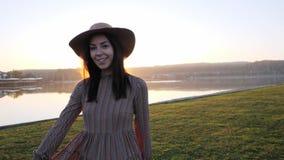 Presentación sonriente de la chica joven adorable en la cámara durante caminar cerca del lago metrajes
