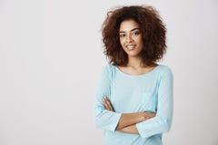 Presentación sonriente de la muchacha africana hermosa con los brazos cruzados sobre el fondo blanco Copie el espacio Fotos de archivo libres de regalías