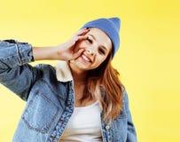 Presentación sonriente feliz de la mujer bastante adolescente de los jóvenes en el fondo amarillo, concepto de la gente de la for Foto de archivo libre de regalías