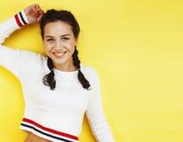 Presentación sonriente feliz de la mujer bastante adolescente de los jóvenes en el fondo amarillo, concepto de la gente de la for Imagen de archivo