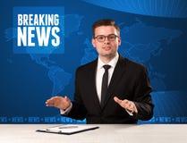 Presentador de la televisión en noticias de última hora que dicen delanteras con el fondo moderno azul foto de archivo libre de regalías