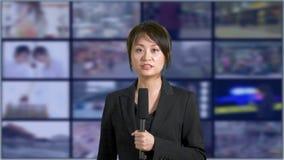 Presentador femenino de las noticias en estudio almacen de metraje de vídeo