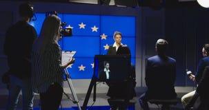 Presentador femenino de las noticias que lee las noticias almacen de metraje de vídeo
