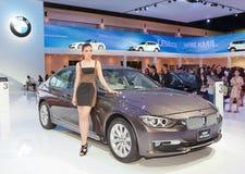 Presentador femenino no identificado con el coche de BMW Fotografía de archivo