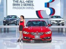 Presentador femenino no identificado con el coche de BMW 320d Foto de archivo