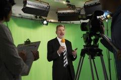 Presentador masculino In Television Studio con el equipo en primero plano foto de archivo