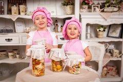 Presentadoras del cocinero de los jóvenes con la comida en botella sabrosa foto de archivo