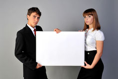 Presentation. Young man and women showing blank white board Stock Photos