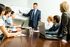 Presentation. Image of smart business people listening to confident man while he explaining something on whiteboard during seminar Royalty Free Stock Photography