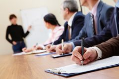 At presentation. Row of business people making notes during presentation Stock Image