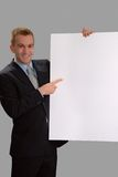 Presentation. Young male professional holding a large blank white paper with room for your message--with clipping path Stock Images
