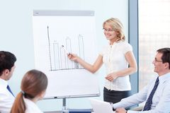 Presentation. An attractive woman tells a presentation at the office Stock Image