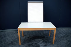 Presentation. Whiteboard and wooden table, standing in the foreground of grey background Royalty Free Stock Image
