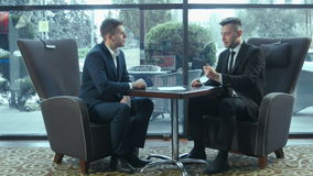 Presentation of the business plan using the touchpad. The businessman explains the business plan and shows to the interlocutor on the touchpad stock footage