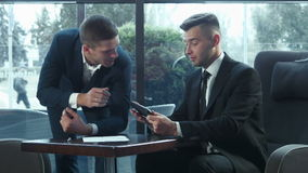 Presentation of the business plan using the touchpad. The businessman explains the business plan and shows to the interlocutor on the touchpad stock video footage